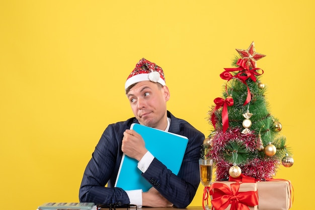 Vooraanzicht van de zakenman die zijn documenten stevig vasthoudt aan de tafel in de buurt van de kerstboom en presenteert op geel