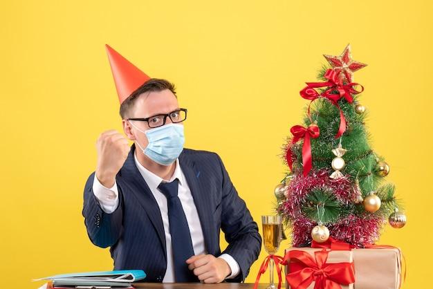 Vooraanzicht van de zakenman met feestmuts achter de tafel in de buurt van de kerstboom en presenteert op geel