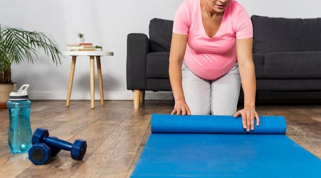 Vooraanzicht van de zwangere vrouw die oefeningsmat thuis oprollen