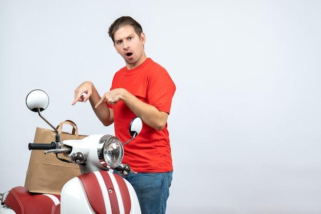 Vooraanzicht van denken bezorger in rode uniform staande in de buurt van scooter aanwijsapparaat op witte achtergrond