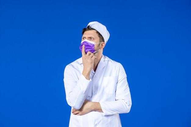 Vooraanzicht van denkende mannelijke arts in medisch kostuum en paars masker op blauw