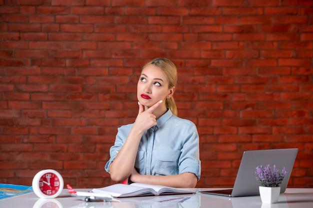 Vooraanzicht van denkende reisagent zit achter haar werkplek bezetting globale assistent binnen toerisme manager bureau kaartservice