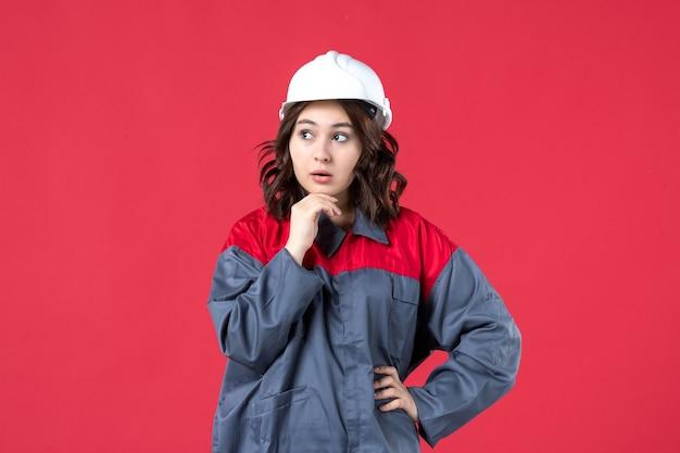 Vooraanzicht van denkende vrouwelijke bouwer in uniform met helm op geïsoleerde rode achtergrond