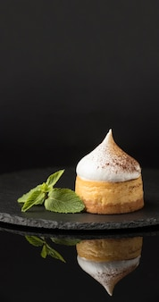 Vooraanzicht van dessert op leisteen met munt en cacaopoeder