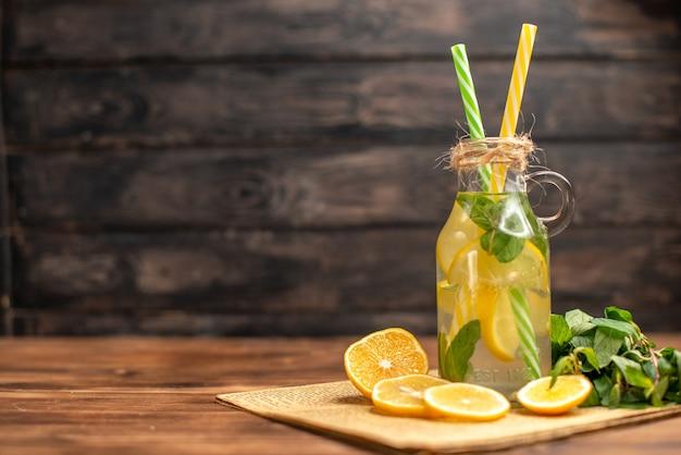 Vooraanzicht van detoxwater gemaakt van citroen en munt op een oude krant aan de linkerkant op bruine houten ondergrond