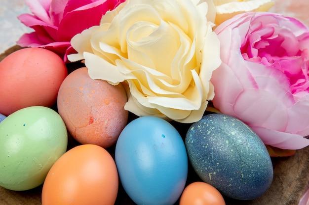 Vooraanzicht van dichtbij gekleurde paaseieren met bloemen op bruine achtergrond sierlijke vakantie horizontale kleurrijke lente pasen concept