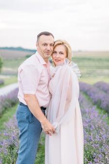 Vooraanzicht van dichtbij van een mooi volwassen stel op het lavendelveld, hand in hand en knuffelen. foto van zorgzame man en vrouw die buiten in het lavendelveld lopen