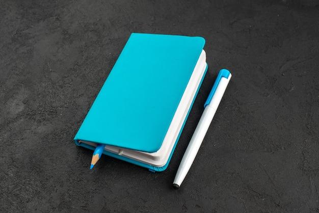 Vooraanzicht van dichtbij van pen in gesloten blauw notitieboekje en pen op zwart