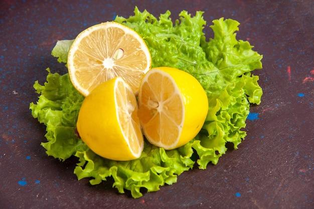 Vooraanzicht van dichtbij verse citroenschijfjes met groene salade op donkere ruimte