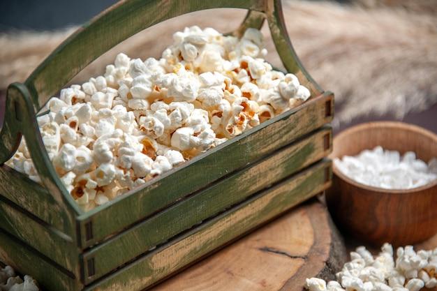 Vooraanzicht van dichtbij verse popcorn op het donkere oppervlak snack popcorn maïsvoedsel