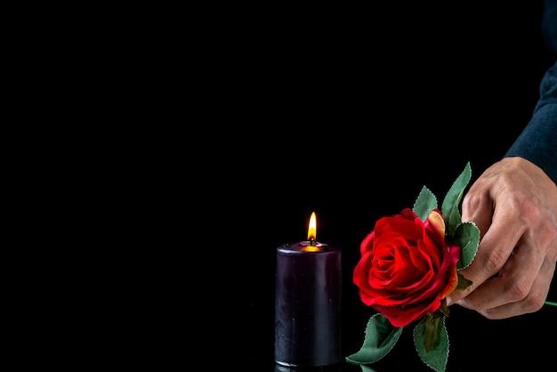 Vooraanzicht van donkere kaars met rode roos en mannenhand op donkere ondergrond