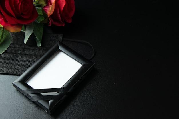 Vooraanzicht van donkere kaars met rode roos op het donkere oppervlak Premium Foto