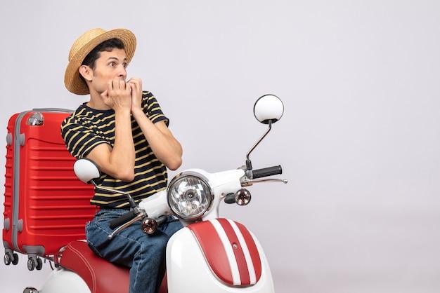 Vooraanzicht van doodsbang jonge man met strooien hoed op bromfiets