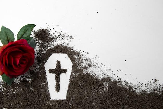 Vooraanzicht van doodskistvorm met donkere grond en rode bloem op wit oppervlak