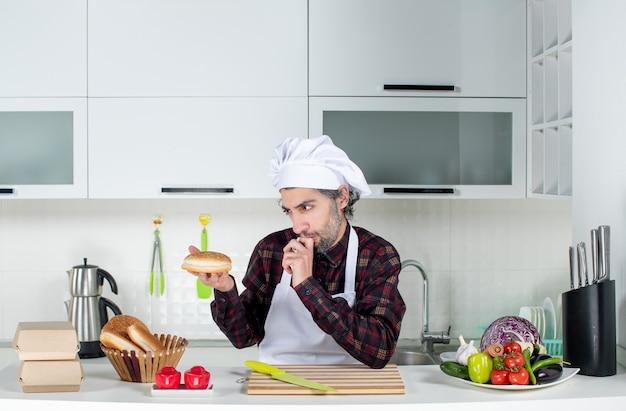 Vooraanzicht van doordachte mannelijke chef-kok die naar brood in de keuken kijkt