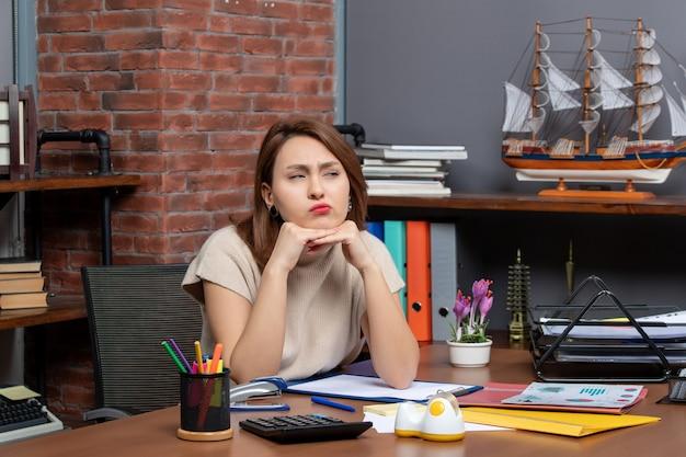 Vooraanzicht van doordachte vrouw die op kantoor werkt
