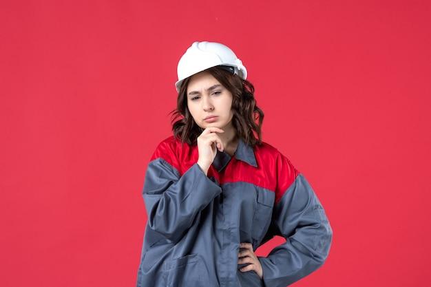 Vooraanzicht van doordachte vrouwelijke bouwer in uniform met helm op geïsoleerde rode achtergrond