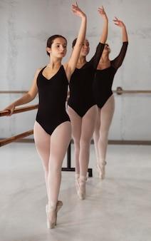 Vooraanzicht van drie ballerina's die repeteren terwijl ze maillots dragen
