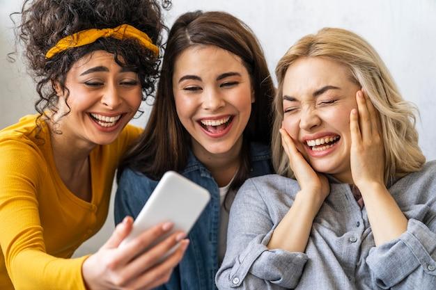 Vooraanzicht van drie gelukkige vrouwen die en een selfie glimlachen nemen
