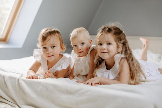 Vooraanzicht van drie schattige kleine meisjes die op bed in de kamer liggen en naar de camera kijken