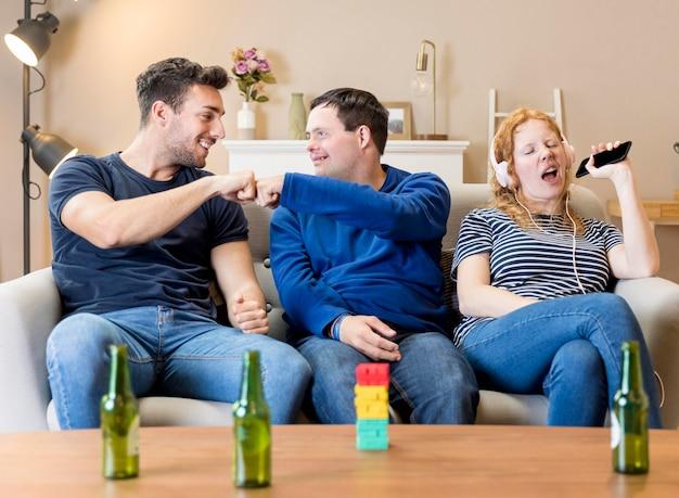 Vooraanzicht van drie vrienden die samen thuis pret hebben