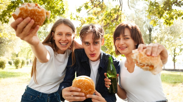 Vooraanzicht van drie vrienden in het park met hamburgers en bier