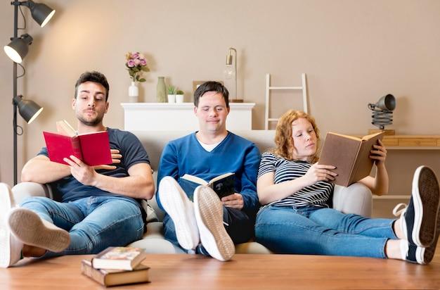 Vooraanzicht van drie vrienden thuis met boeken