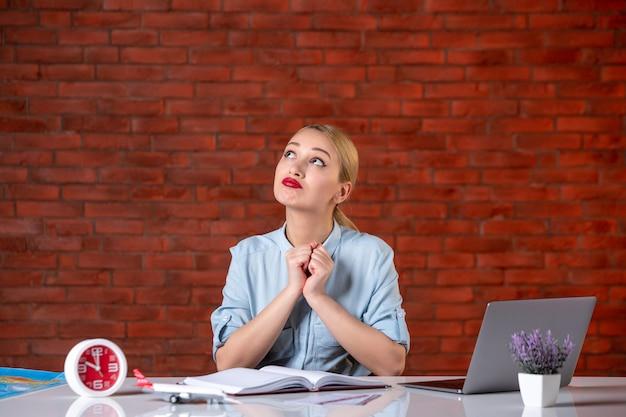Vooraanzicht van dromende reisagent zit achter haar werkplek toerisme bezetting globale service kaartservice binnenshuis bureau manager assistent