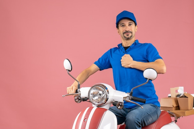 Vooraanzicht van een ambitieuze koeriersman met een hoed die op een scooter zit en zijn gespierd laat zien op een pastelkleurige perzikachtergrond