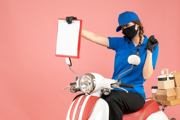 Vooraanzicht van een ambitieuze koeriersvrouw met een medisch masker en handschoenen die op een scooter zit en lege vellen papier vasthoudt die bestellingen afleveren op een pastelkleurige perzikachtergrond