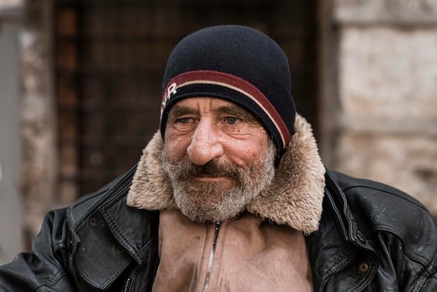 Vooraanzicht van een bebaarde dakloze man buitenshuis