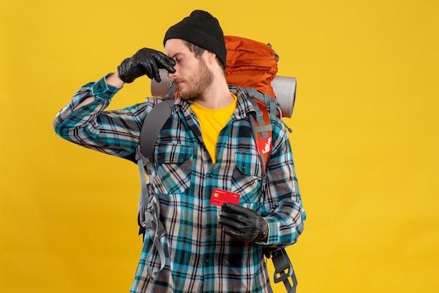 Vooraanzicht van een bebaarde jonge man met backpacker en creditcard met neus