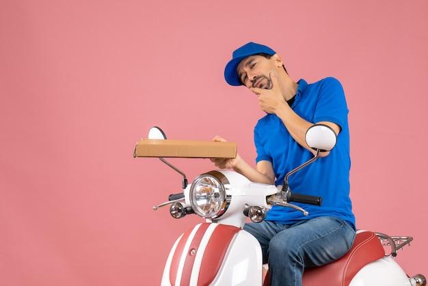 Vooraanzicht van een bedachtzame koeriersman met een hoed die op een scooter zit en de bestelling vasthoudt op een pastelkleurige perzikachtergrond