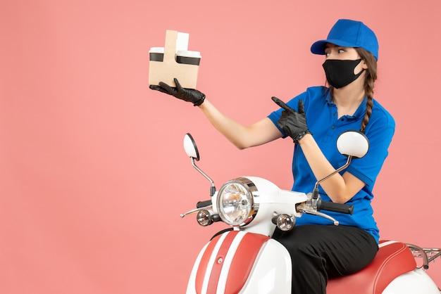 Vooraanzicht van een benieuwde vrouwelijke bezorger met een medisch masker en handschoenen die op een scooter zit en bestellingen aflevert op een pastelkleurige perzikachtergrond