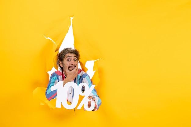 Vooraanzicht van een bezorgde jongeman die tien procent vasthoudt en diep nadenkt in een gescheurd gat in geel papier