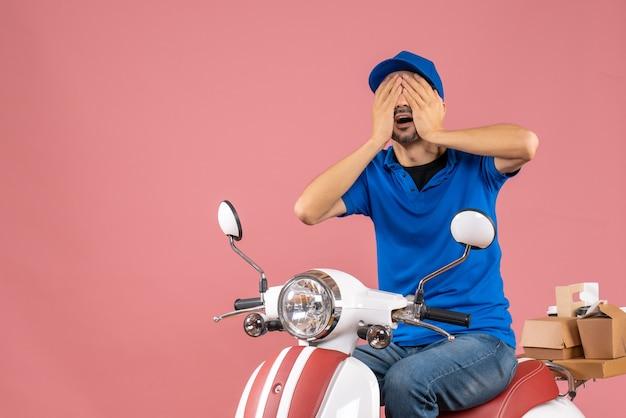 Vooraanzicht van een bezorger met een hoed die op een scooter zit en zijn ogen sluit op een pastelkleurige perzikachtergrond
