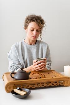 Vooraanzicht van een blonde vrouw met krullend haar die thee drinkt en ontspant