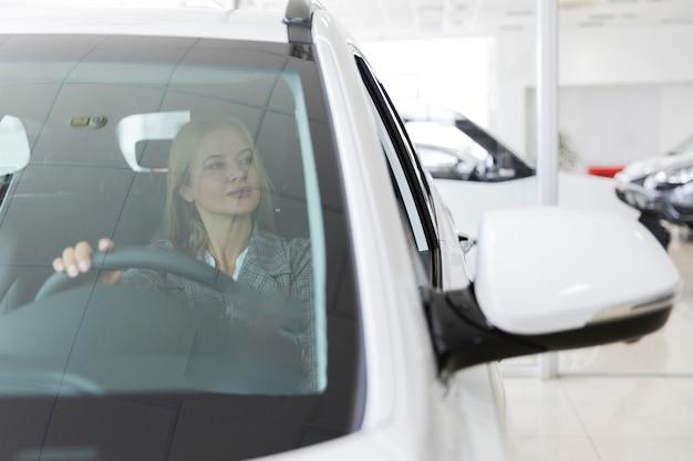 Vooraanzicht van een blondevrouw in de auto