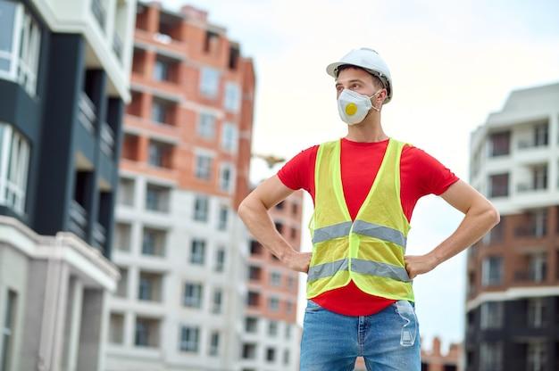 Vooraanzicht van een bouwvakker met een beschermend masker en een reflecterend vest tussen nieuwe gebouwen