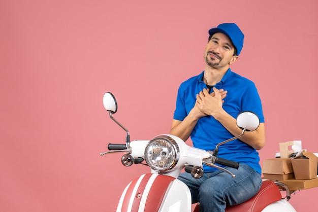 Vooraanzicht van een dankbare jonge koeriersman met een hoed die op een scooter zit en zijn handen op de borst houdt op een pastelkleurige perzikachtergrond
