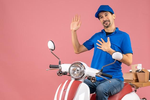 Vooraanzicht van een dankbare koeriersman met een hoed die op een scooter zit op een pastelkleurige perzikachtergrond