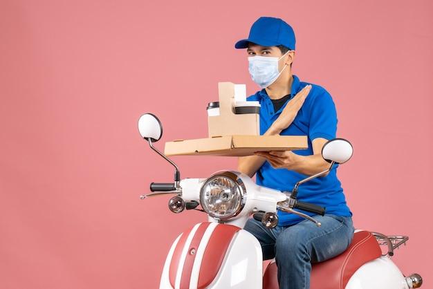 Vooraanzicht van een dankbare mannelijke bezorger met een masker met een hoed op een scooter met bestellingen op een pastelkleurige perzikachtergrond