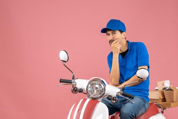 Vooraanzicht van een denkende bezorger met een hoed die op een scooter zit op een pastelkleurige perzikachtergrond