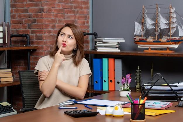 Vooraanzicht van een denkende leuke vrouw die op kantoor werkt