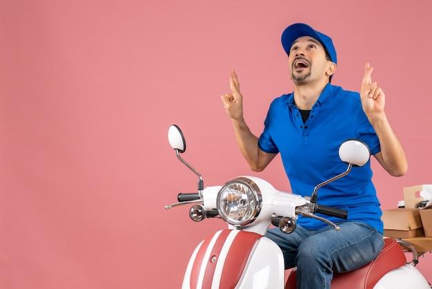 Vooraanzicht van een dromerige koeriersman met een hoed die op een scooter zit op een pastelkleurige perzikachtergrond