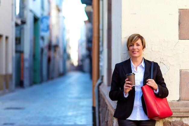 Vooraanzicht van een elegante bedrijfsvrouw die en zich op een straatmuur bevindt leunt