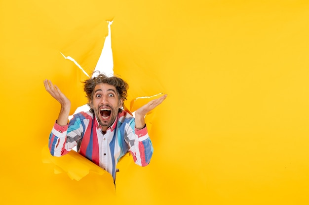 Vooraanzicht van een emotionele en gekke jonge kerel die lacht door een gescheurd gat in geel papier
