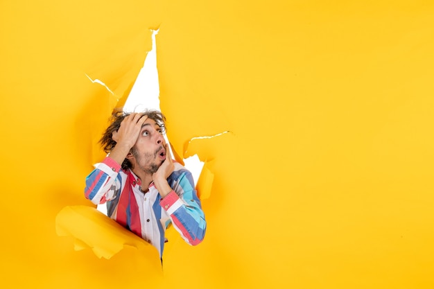 Vooraanzicht van een emotionele en gekke uitgeputte jonge kerel die omhoog kijkt door een gescheurd gat in geel papier