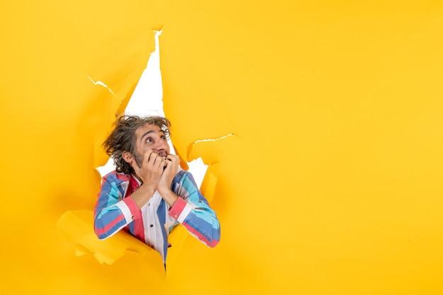 Vooraanzicht van een emotionele en gekke uitgeputte jongeman die omhoog kijkt door een gescheurd gat in geel papier