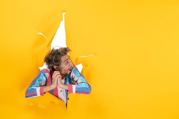 Vooraanzicht van een emotionele en uitgeputte jonge kerel geconcentreerd op iets door een gescheurd gat in geel papier in